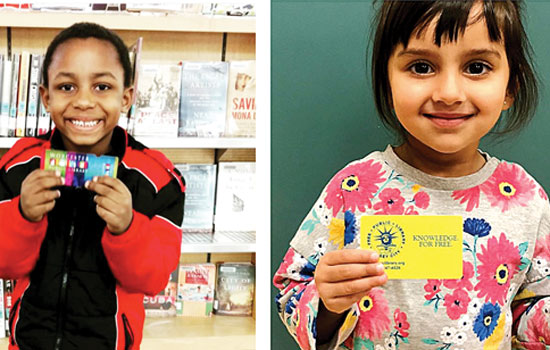 Children hold up library cards