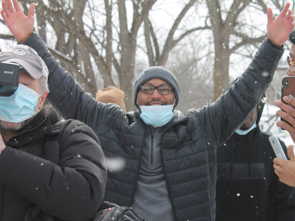 Kenneth Nixon stands outside in the snow, raising his arms triumphantly.